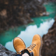 Feet of traveler in boots over chasm with river canyon - PhotoDune Item for Sale