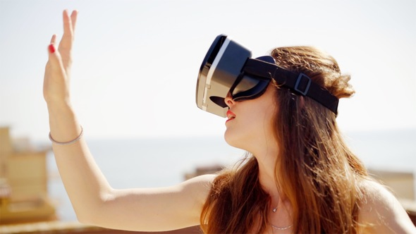 Happy Young Woman Uses a Virtual Reality Glasses on the Roof. Future Is Right Now.