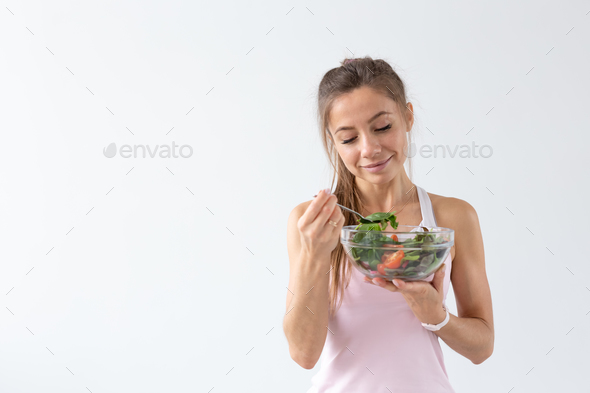 People, food and diet concept - Portrait of woman eating healthy food over white background with - Stock Photo - Images