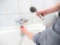 Plumber unscrewing shower hose - PhotoDune Item for Sale