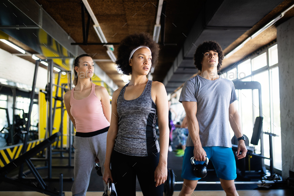 Healthy young athletes doing exercises at fitness studio - Stock Photo - Images
