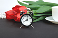 Black alarm clock near bouquet red tulips - PhotoDune Item for Sale