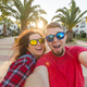 Travel, vacation and holiday concept - Happy couple having fun taking selfie over park with palms - PhotoDune Item for Sale