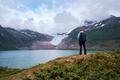 Girl tourist looks at a glacier. Svartisen Glacier in Norway. - PhotoDune Item for Sale