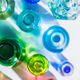 Glass bottle assortment with colorful shadows and flares on a white background with copy space - PhotoDune Item for Sale