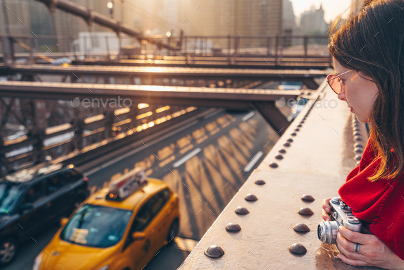 Attractive girl with a camera on Brooklyn Bridge - Stock Photo - Images