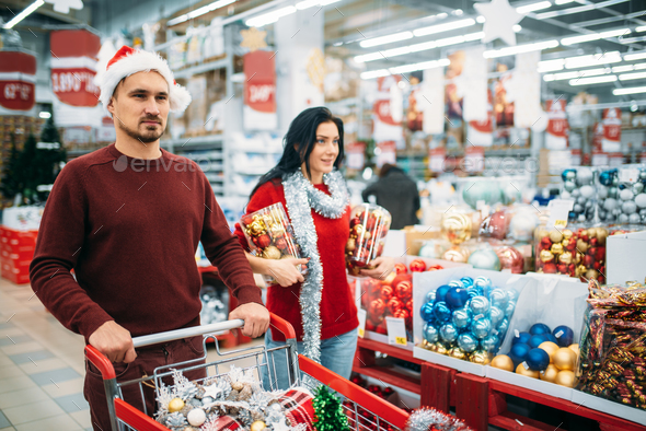 Young couple buying a lot of Christmas decorations - Stock Photo - Images