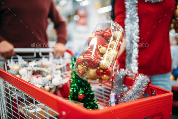 Young couple put in a cart Christmas decorations - Stock Photo - Images