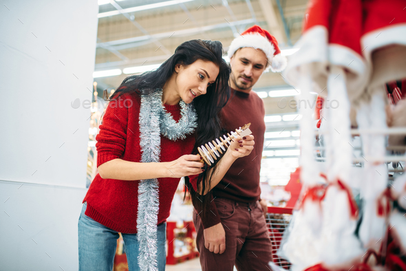 Couple chooses christmas souvenir in supermarket - Stock Photo - Images