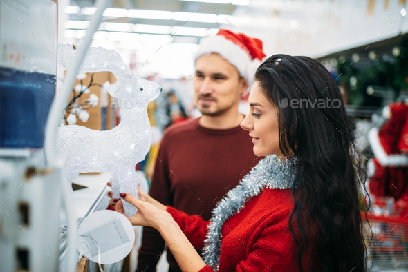 Couple looks on glass deer in supermarket - Stock Photo - Images