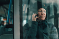 Woman talking on mobile phone in public bus in winter - PhotoDune Item for Sale