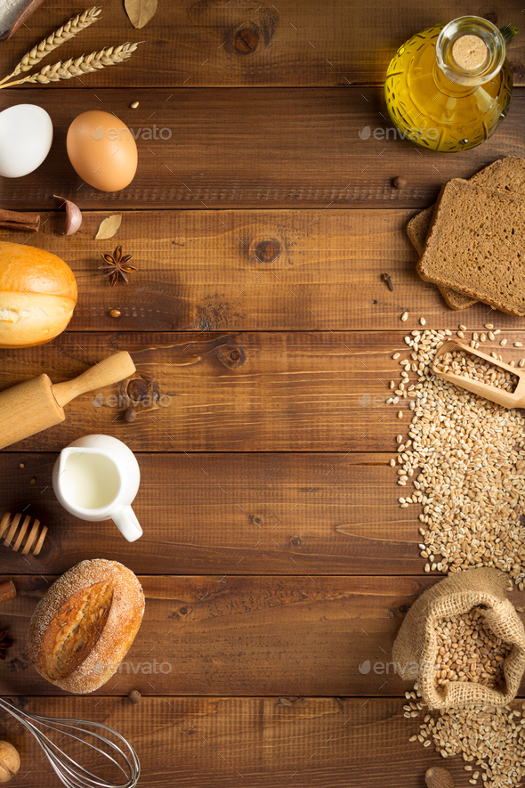 wheat grains and bakery ingredients on wood - Stock Photo - Images