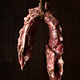 whole raw pork rib hanging in front of a wooden background - PhotoDune Item for Sale