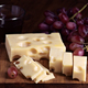 Wine grape and portions of Spanish cheese on wood with selective light - PhotoDune Item for Sale