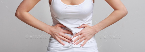 Woman with stomachache, having food poisoning, grey background - Stock Photo - Images