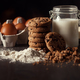 Chocolate cookies on rustic wooden table with bottle of milk, white flour, fresh eggs,butter and - PhotoDune Item for Sale