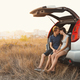 Cute young couple in love sitting in a car with an open trunk hu - PhotoDune Item for Sale