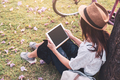 Young woman relaxing and using tablet and surf internet in the park - PhotoDune Item for Sale
