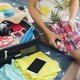 Young woman traveler packing her clothes and stuff in suitcase - PhotoDune Item for Sale