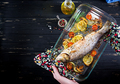 Baked sea bass in a baking dish with spices and vegetables  to hold in hands.  - PhotoDune Item for Sale