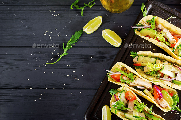 Mexican tacos with chicken meat, avocado, tomato, cucumber and red onion.  - Stock Photo - Images