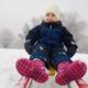 Little girl enjoying a sleigh ride. Child sledding. Toddler kid riding a sledge - PhotoDune Item for Sale