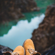 Feet of traveler in boots sitting over river canyon - PhotoDune Item for Sale