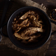 Homemade stew of lamb's liver and garlics on rustic wooden board illuminated in chiaroscuro - PhotoDune Item for Sale