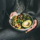 Woman holding bowl with fresh salad, avocado, beans and vegetables - PhotoDune Item for Sale