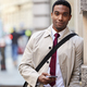 Young black businessman in the street in London holding phone and smiling to camera - PhotoDune Item for Sale