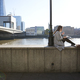 Two millennial colleagues take a break sitting on the embankment eating near London Bridge - PhotoDune Item for Sale
