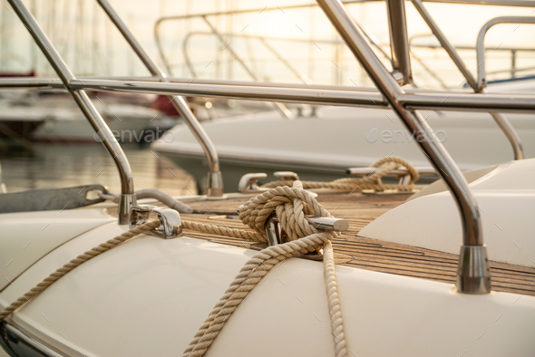 White mooring rope tied around steel anchor on boat - Stock Photo - Images