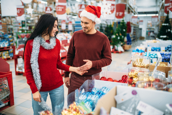 Young couple chooses christmas tree toys in shop - Stock Photo - Images