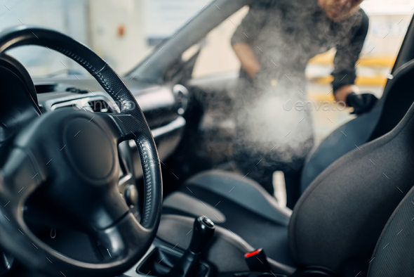 Cleaning of car salon with steam cleaner - Stock Photo - Images