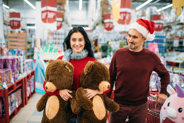 Couple with two big plush bears in supermarket - Stock Photo - Images
