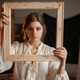 Female painter holds wooden frame at her face - PhotoDune Item for Sale