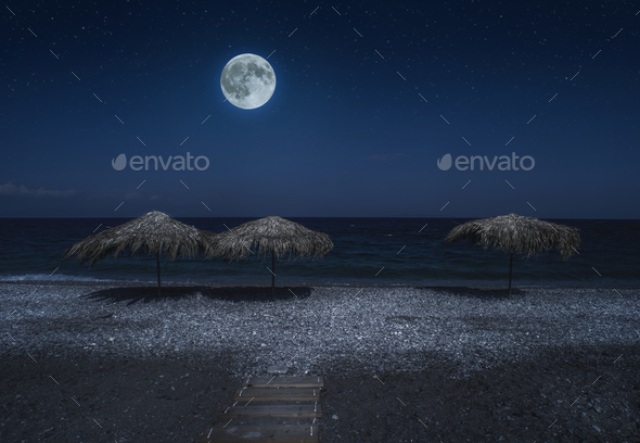 Straw umbrellas on the beach in the night. Moonlight on sea. Nig - Stock Photo - Images