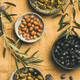 Mediterranean pickled olives and olive tree branches, yellow background - PhotoDune Item for Sale
