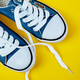 Blue female or male sneakers on yellow paper background. - PhotoDune Item for Sale