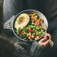 Woman holding bowl with healthy vegetarian dinner, top view - PhotoDune Item for Sale