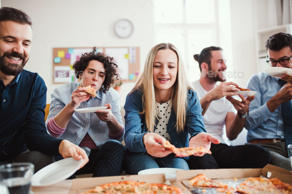 Group of young businesspeople with pizza having lunch in a modern office. - Stock Photo - Images