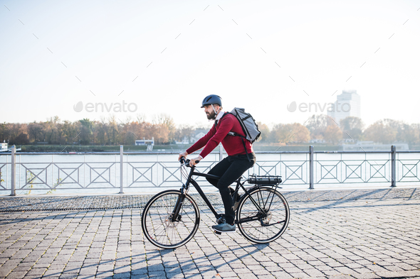 Hipster businessman commuter with electric bicycle traveling to work in city. - Stock Photo - Images