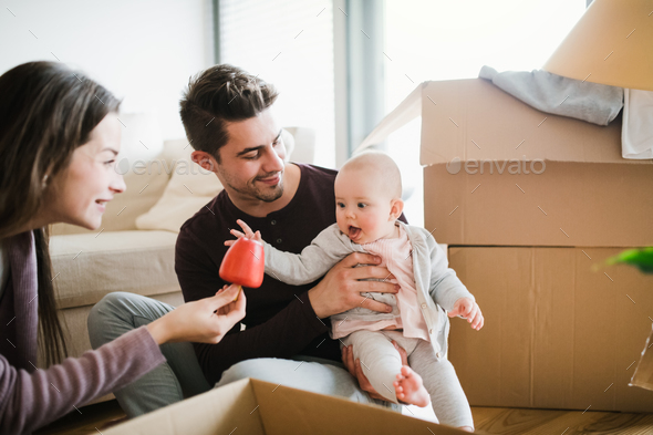 Young couple with a baby and cardboard boxes moving in a new home. - Stock Photo - Images