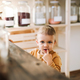 A small toddler boy standing at the counter in zero waste shop. - PhotoDune Item for Sale