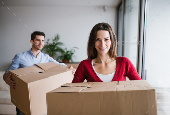 Young couple with cardboard boxes moving in a new home. - Stock Photo - Images