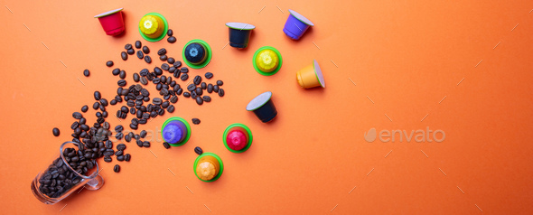 Coffee beans and capsules on orange color background, banner - Stock Photo - Images