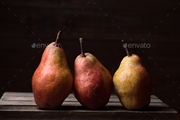 pears in row on rustic wooden boards in dark stage - Stock Photo - Images