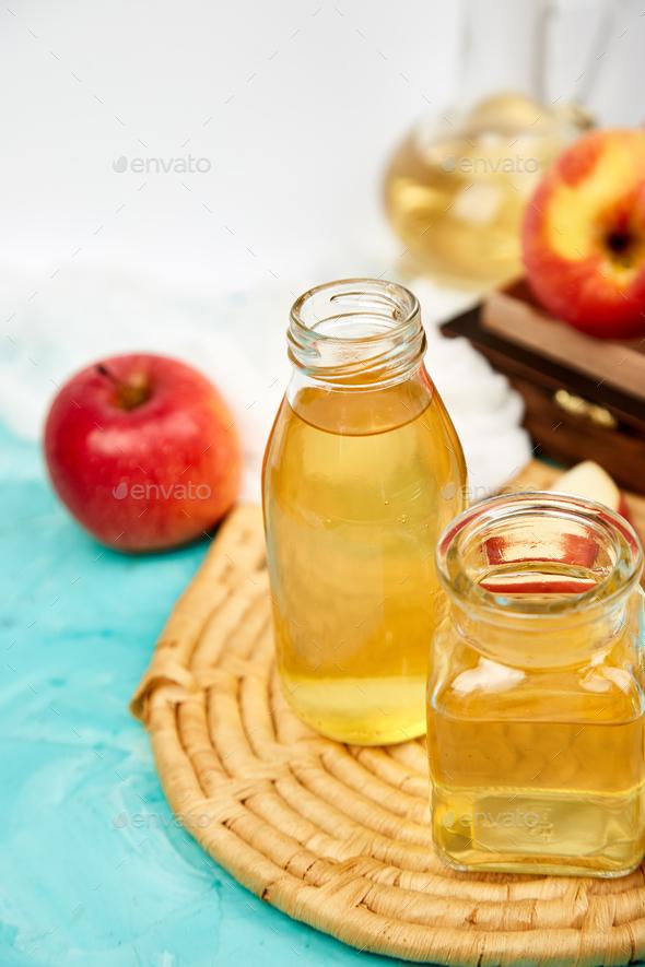Glass Bottle of apple organic vinegar on blue background. - Stock Photo - Images