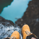 Feet of nature explorer in boots sitting over river canyon - PhotoDune Item for Sale