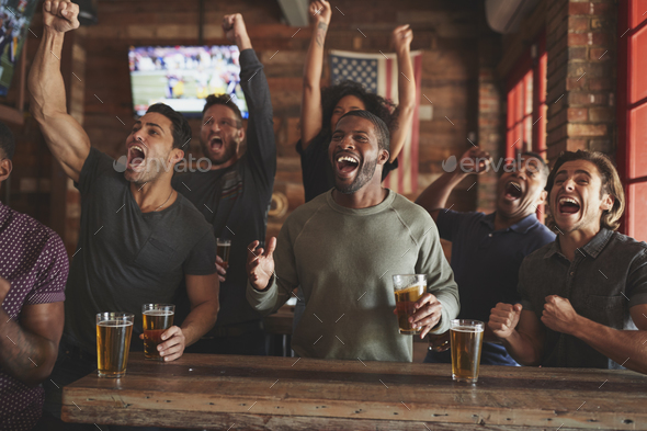 Group Of Male Friends Celebrating Whilst Watching Game On Screen In Sports Bar - Stock Photo - Images